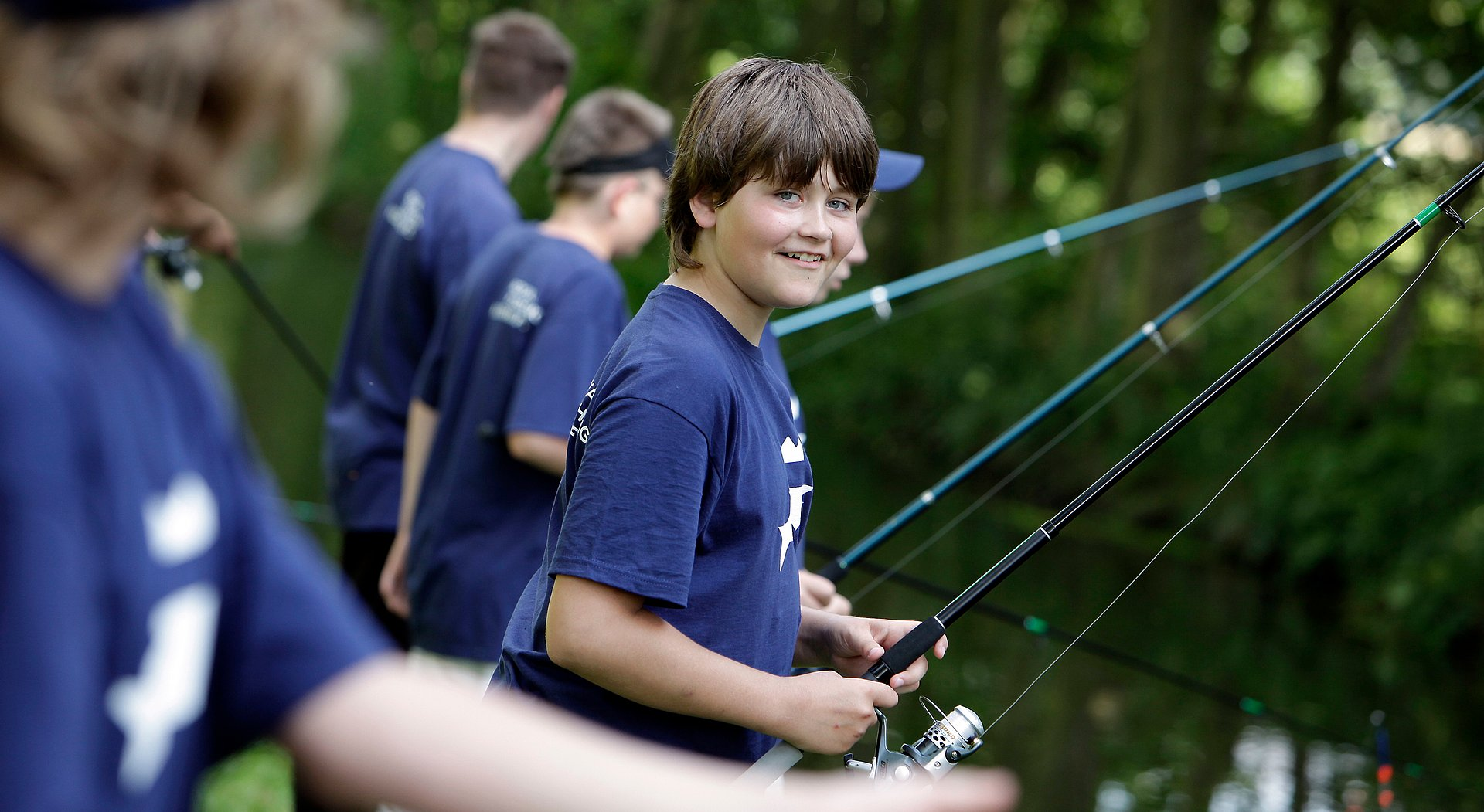Kinder mit T-Shirts im Royal Fishing Corporate Design angeln gemeinsam am See